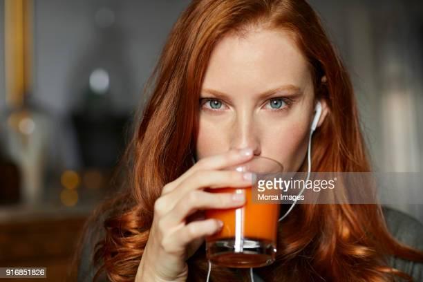 Porträt Frau mit Kopfhörern Saft zu trinken