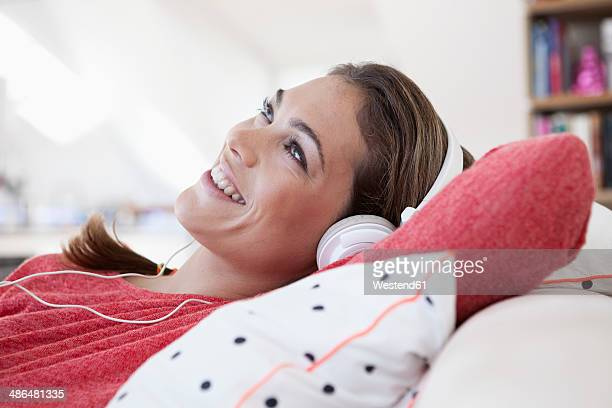 Portrait of woman with headphones lying on a couch in her apartment