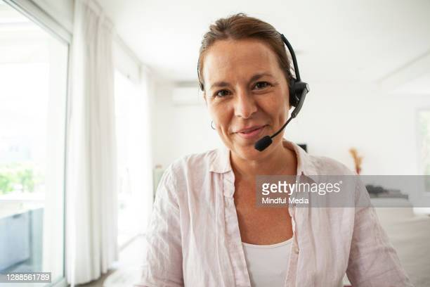 portrait of woman with headset - front view stock pictures, royalty-free photos & images