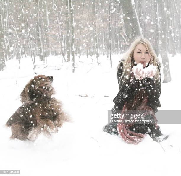 Portrait of woman with her dog in snow