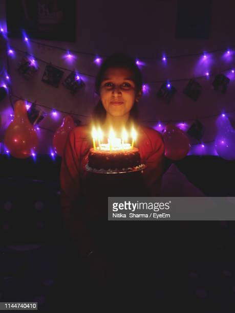 Portrait Of Woman With Illuminated Candles On Cake