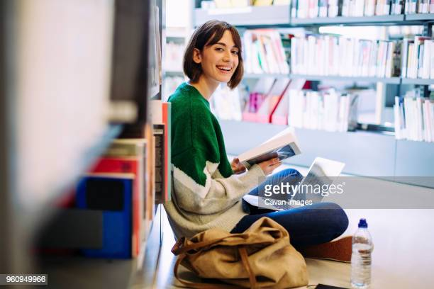 portrait of woman with laptop computer reading book while sitting on floor in library - studenten stock-fotos und bilder