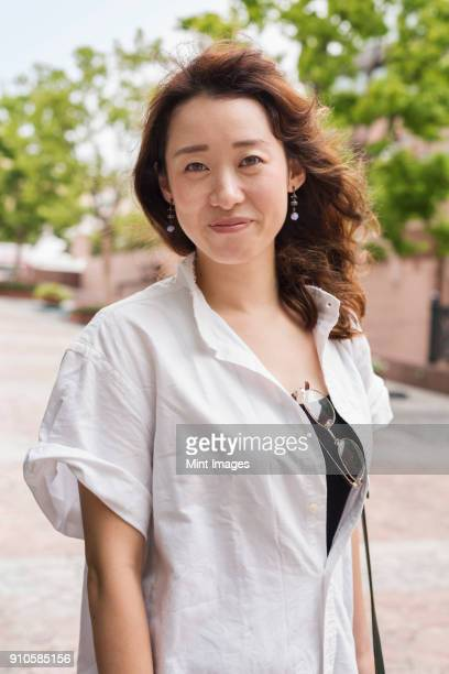 portrait of woman with long brown hair wearing white standing outdoors, smiling at camera. - 30代の女性 ストックフォトと画像