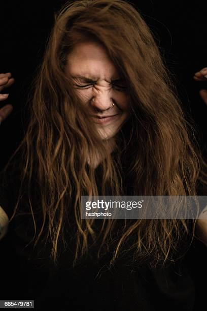 portrait of woman with long brunette hair, eyes closed making face - heshphoto stock pictures, royalty-free photos & images