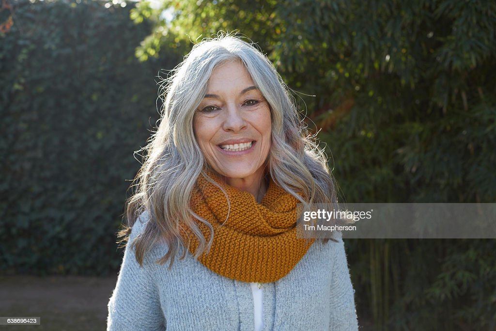 Portrait of woman with long gray hair looking at camera smiling : Stock Photo