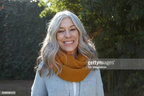 portrait of woman with long gray hair looking at camera smiling - baby boomer stock-fotos und bilder