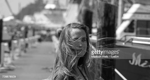 Portrait Of Woman With Long Hair On Pier At Harbor