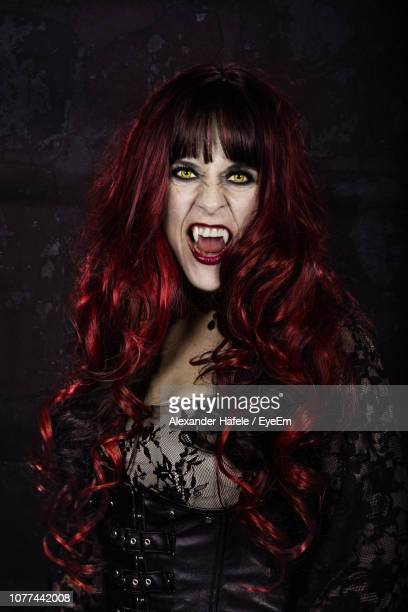 portrait of woman with long hair wearing costume during halloween against black background - vampire stock photos and pictures