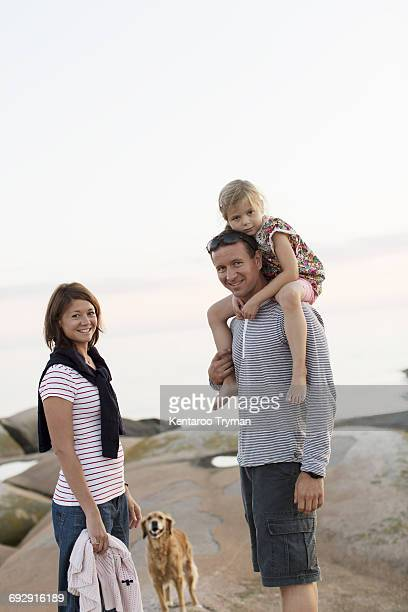 portrait of woman with man carrying girl on shoulder standing against sky - einzelnes tier stock-fotos und bilder