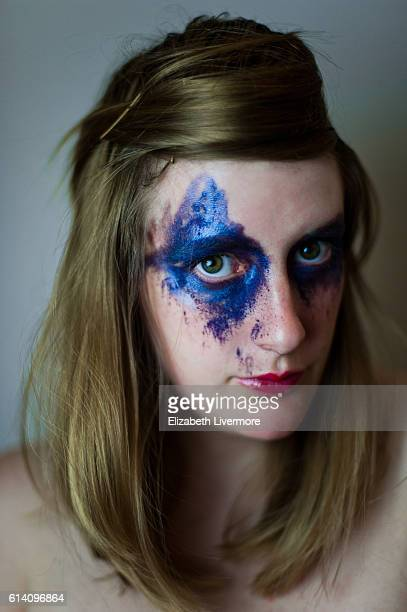 Portrait of woman with messy face paint