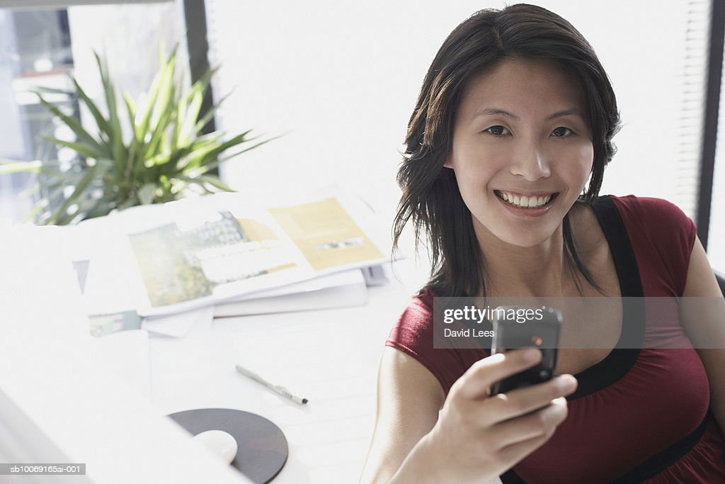 Portrait of woman with mobile phone in office : Stockfoto