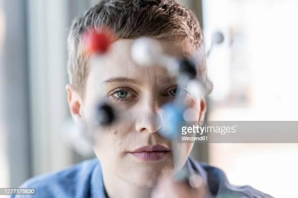 portrait of woman with molecule model - wissenschaftlerin stock-fotos und bilder