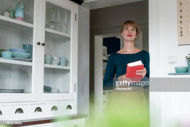 portrait of woman with novel lening against door case at home - mid adult stock pictures, royalty-free photos & images