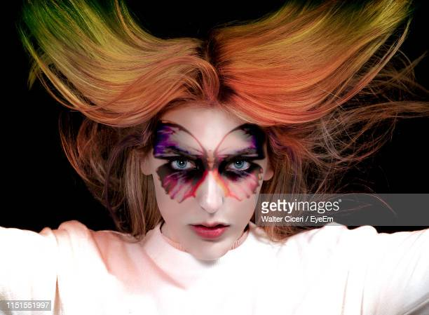 portrait of woman with painted face and dyed hair against black background - walter ciceri foto e immagini stock