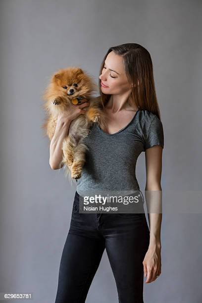 Portrait of Woman with pet dog on grey backdrop