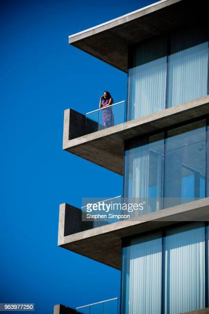 portrait of woman with phone on balcony of city high-end condo - capital architectural feature stock pictures, royalty-free photos & images