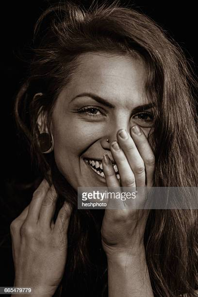portrait of woman with piercings, hand over mouth, looking at camera smiling - heshphoto stock pictures, royalty-free photos & images