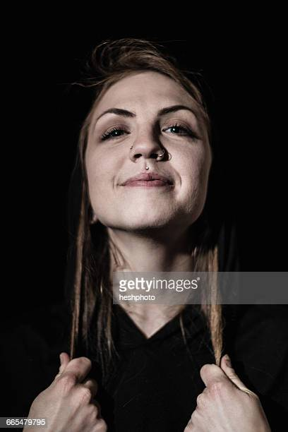 portrait of woman with piercings looking at camera smiling - heshphoto stock-fotos und bilder