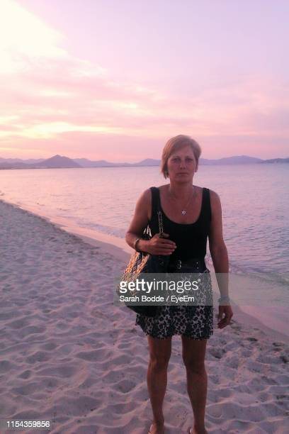 portrait of woman with purse standing at sandy beach during sunset - sarah sands stock pictures, royalty-free photos & images