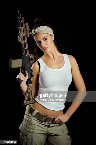 portrait of woman with rifle standing against black background - ライフル ストックフォトと画像