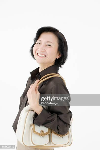 Portrait of woman with shoulder bag, smiling, studio shot
