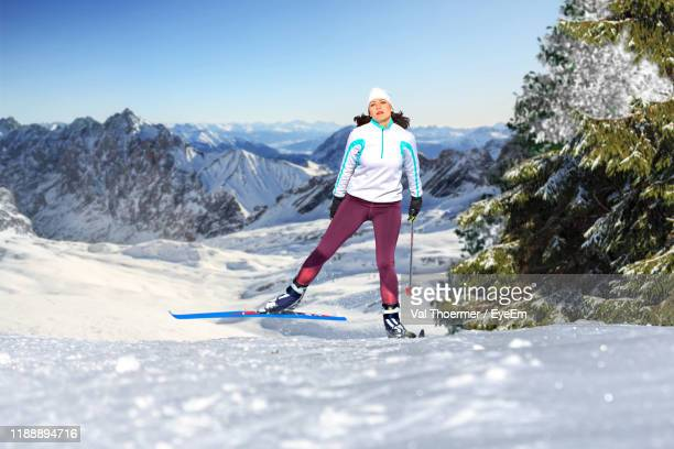 portrait of woman with ski-wear standing on snow against mountains - val thoermer stock-fotos und bilder