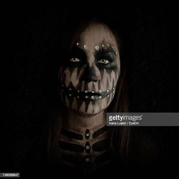 Portrait Of Woman With Skull Face Paint Against Black Background
