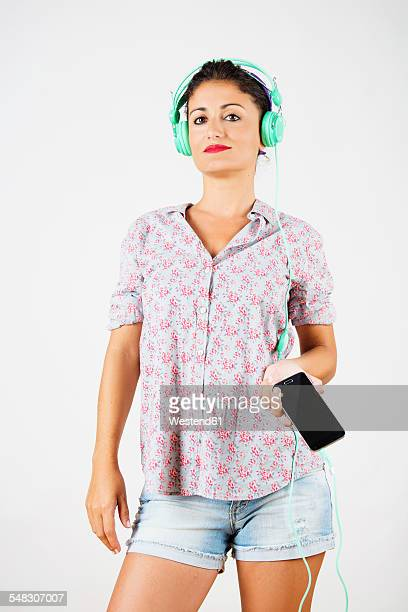 portrait of woman with smartphone and headphones listening music - chemisier photos et images de collection