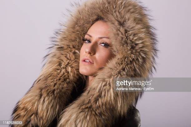 portrait of woman with snow against gray background - fur hat stock pictures, royalty-free photos & images