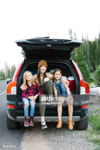 Portrait of woman with son (6-7) and daughter (8-9) in back of car