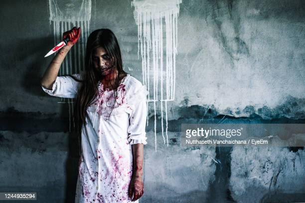 portrait of woman with spooky make-up holding knife while standing against wall - crime and murder stock pictures, royalty-free photos & images