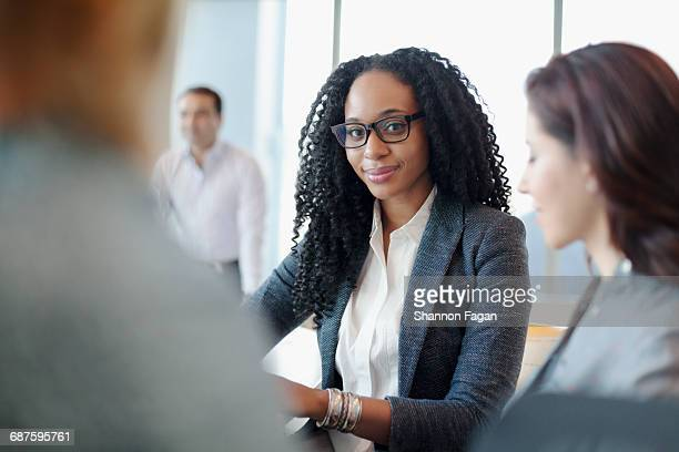 Portrait of woman with staff in office meeting