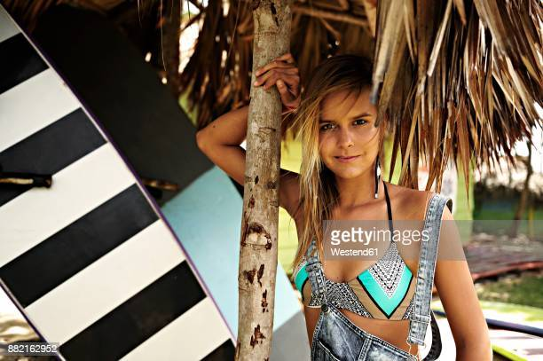 Portrait of woman with surfboard under straw roof