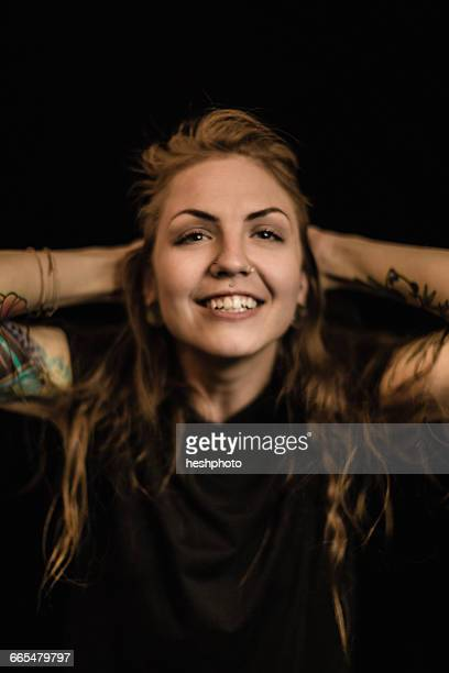 portrait of woman with tattoo and piercings, hands behind head looking at camera smiling - heshphoto foto e immagini stock