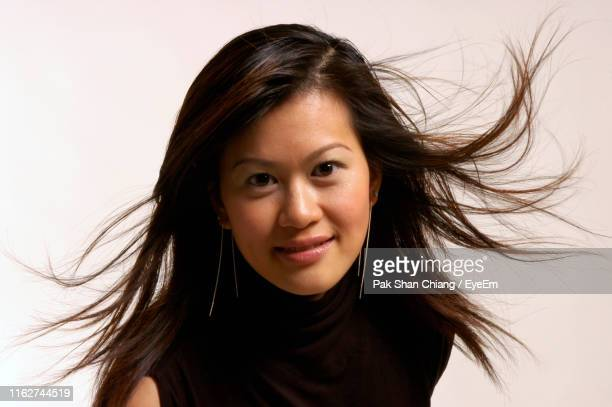 portrait of woman with tousled hair against white background - 黒髪 ストックフォトと画像