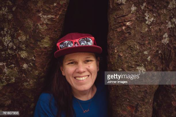 Portrait of woman with tree trunk