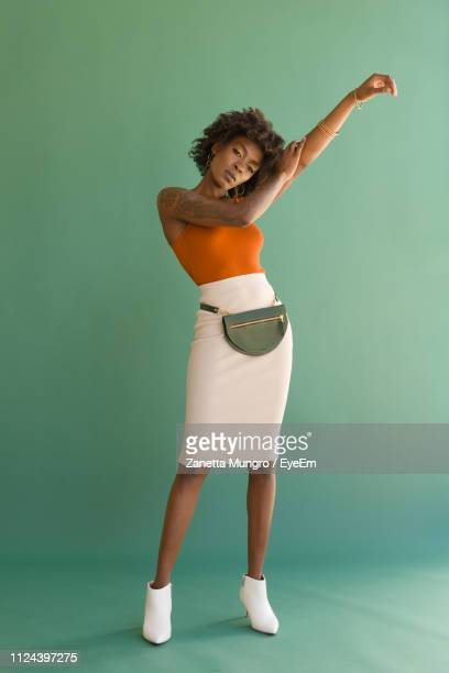 portrait of woman with waist pack against green background - borsetta da sera foto e immagini stock