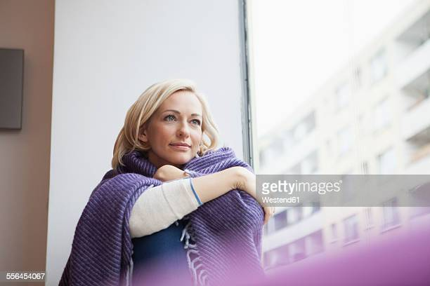 Portrait of woman with woolen blanket looking through window