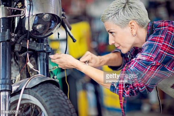portrait of woman working in custom motorcycle garage - dismantling stock pictures, royalty-free photos & images