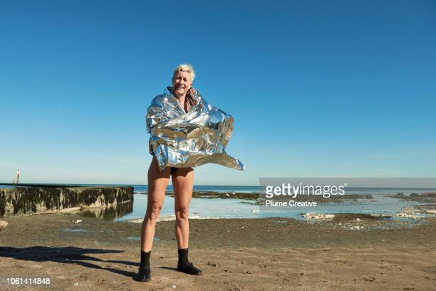 portrait of woman wrapped in foil blanket after a swim in the sea - goose bumps stock pictures, royalty-free photos & images