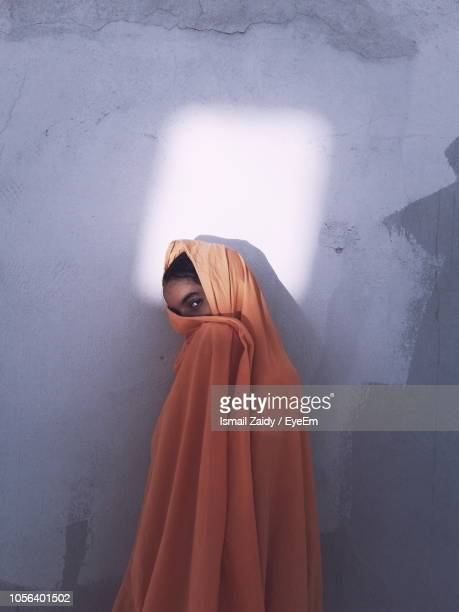 portrait of woman wrapped in textile standing against wall at home - marruecos fotografías e imágenes de stock