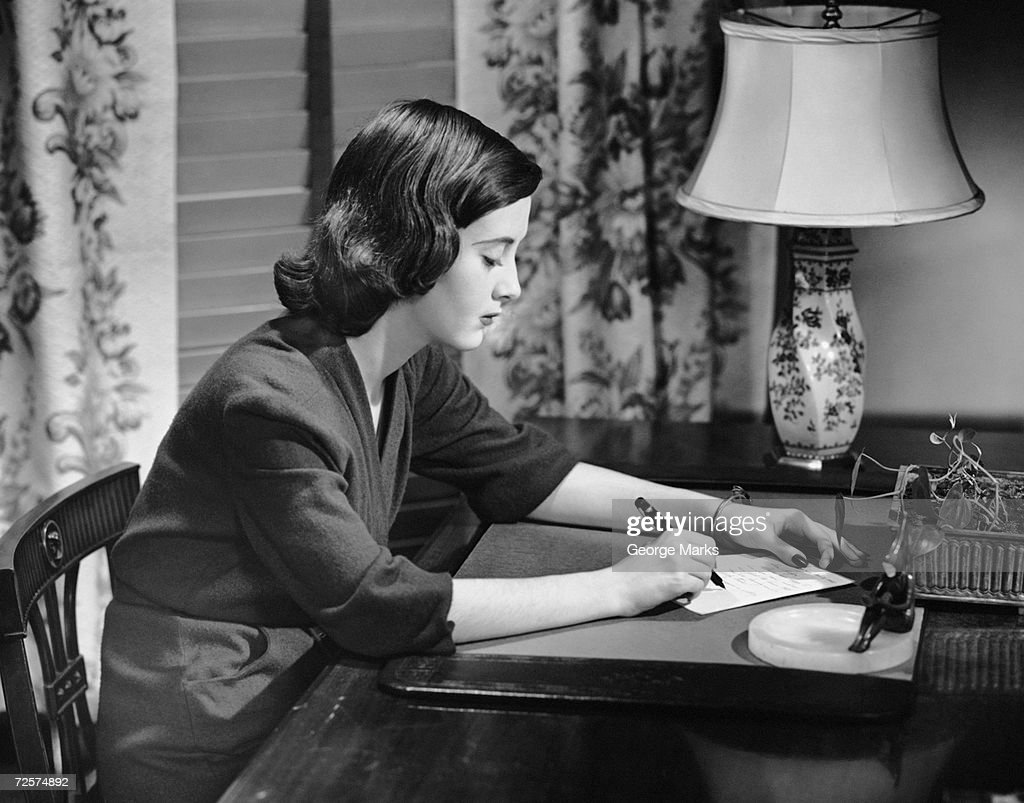 Portrait of woman writing letter at desk : News Photo