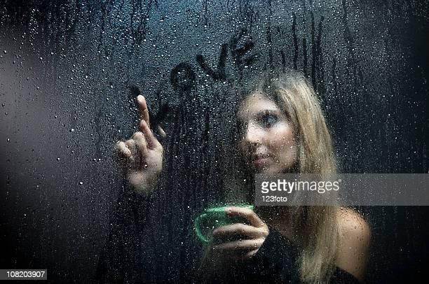 Portrait of Woman Writing 'Love' on Wet Window