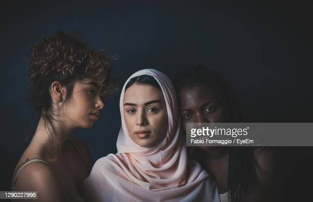 portrait of women embracing while standing against black background - religious veil stock pictures, royalty-free photos & images