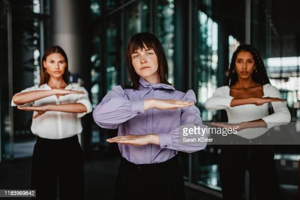 portrait of women gesturing equal sign while standing against building - igualdad fotografías e imágenes de stock