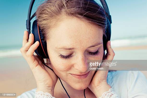 Portrait of women listen to music on beach.