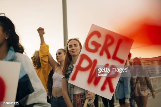 portrait of women protesting with friends for human rights in city against sky - protestor stock pictures, royalty-free photos & images