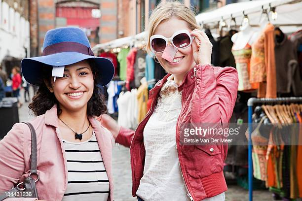 portrait of women trying on hat and sunglasses. - hat stock pictures, royalty-free photos & images