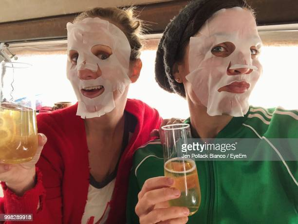 portrait of women wearing facial mask while holding drinks - wirkliches leben stock-fotos und bilder