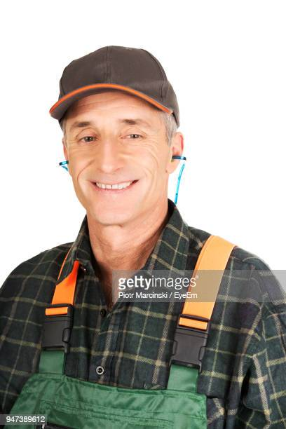 portrait of worker against white background - green hat stock pictures, royalty-free photos & images